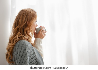 Relaxed Caucasian girl is sitting on a warm floor in a white sweater and socks wrapped in a woolen blanket near the window in light. autumn mood, warmth and comfort. beautiful female in socks