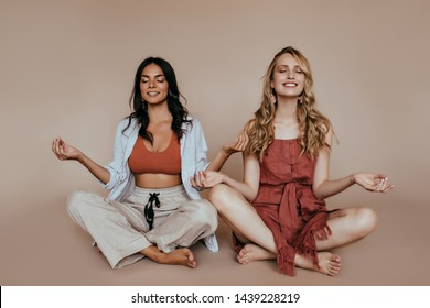 Relaxed caucasian girls doing yoga together. Studio shot of latin woman meditating on the floor.