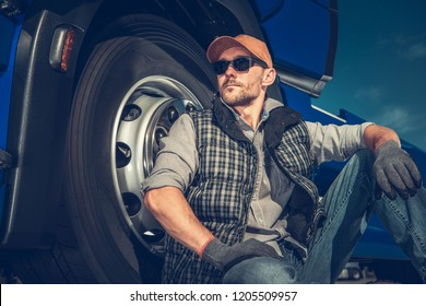 Relaxed Caucasian Truck Driver Seating on the Ground and Support His Back on the Semi Truck Wheel.