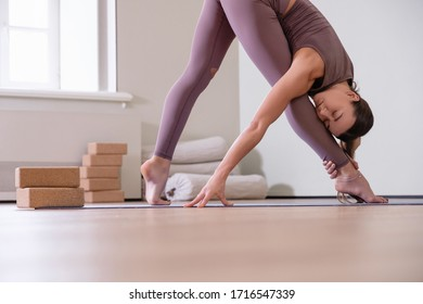 Relaxed caucasian young woman yoga instructor doing parsvottanasana in her cozy apartment. Concept of home workouts during quarantine and strengthening leg muscles. Advertising space