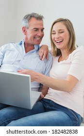 Relaxed cheerful couple using laptop on sofa at home