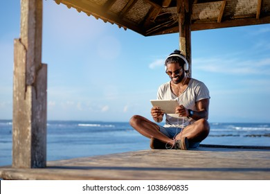 Relaxed and cheerful. Work and vacation. Outdoor portrait of happy young african man using tablet computer on deck near the sea.