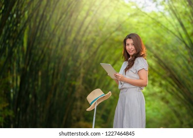Relaxed and cheerful. Work and vacation. Outdoor portrait of happy asian woman using tablet computer with suitcase, hat in the middle of Bamboo grove, Tunnel bamboo trees and walkway.