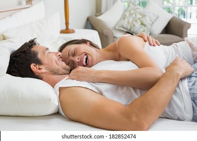 Relaxed cheerful young couple lying together in bed at home