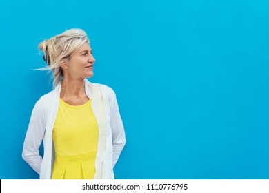 Relaxed confident blond woman against a blue wall standing looking to the side towards blank copy space with a smile