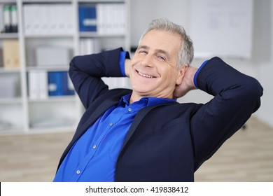 Relaxed confident businessman with a beaming smile sitting back in his chair in the office with his hands clasped behind his head