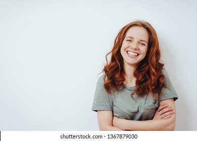Relaxed confident friendly young woman in a casual T-shirt standing with folded arms in front of a white wall with copy space