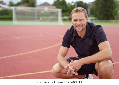 Relaxed confident handsome young sports coach squatting on his haunches on an outdoor race track looking at the camera with a friendly smile