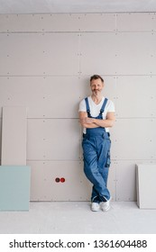 Relaxed confident handyman or DIY homeowner standing in denim dungarees with folded arms leaning on an incomplete clad wall in a new build house