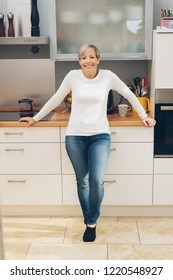 Relaxed confident housewife in her kitchen leaning against the counter looking at the camera with a beaming friendly smile