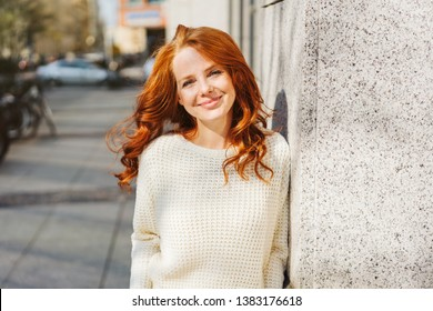 Relaxed confident young redhead woman leaning against a building wall in an urban street looking at the camera with a lovely warm friendly smile