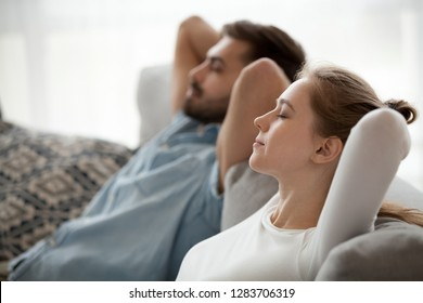 Relaxed couple resting on comfortable couch, happy calm man and woman enjoying relaxation having nap on sofa breathing fresh air feeling relief, peace of mind on stress free day at home concept