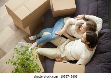 Relaxed couple resting on sofa on moving day, young renters relaxing on couch moved into apartment with boxes, happy satisfied home owners enjoying first day in new house after relocation, top view
