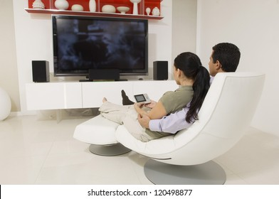 Relaxed couple sitting on a modern chair while watching television