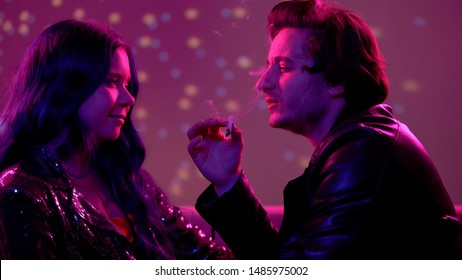 Relaxed couple smoking weed and flirting at night club party, carefree life