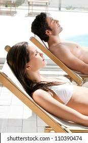 Relaxed couple sunbathing together at swimming pool in summer