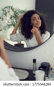 Relaxed curly female is standing in front of mirror in bathroom and using jade roller on cheeks