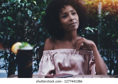 A relaxed curly mixed female is resting in a street bar with a glass of delicious cocktail next to her on the table; charming young biracial woman in an outdoor cafe with the glass of a tasty drink