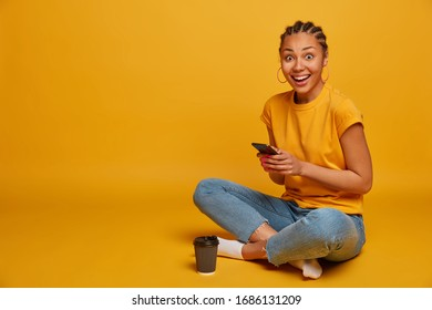 Relaxed dark skinned woman sits crossed legs, dressed in casual t shirt and jeans, uses mobile phone, sends text messages, browses internet, drinks takeaway coffee, scrolls news, isolated on yellow - Shutterstock ID 1686131209