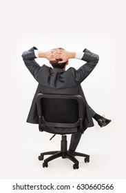 relaxed dreaming businessman sitting in chair inside office against white wall, isolated on white background with clipping path. back rear view. unrecognizable person.  look into the future