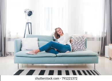 Relaxed dreaming woman at home sitting on sofa