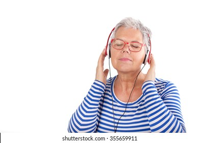 Relaxed elderly woman listening to music with headphones