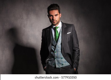 relaxed elegant man with hands in pockets wearing tuxedo with green tie and vest in studio