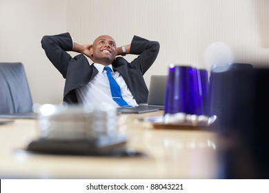 Relaxed executive daydreaming with hands on back of head