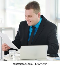Relaxed executive sitting on desk in office and reading letter