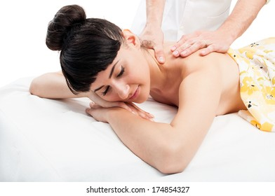 Relaxed female model keeping her eyes closed while is getting a massage at the massage salon.