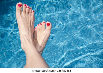 Relaxed female's feet against swimming pool water