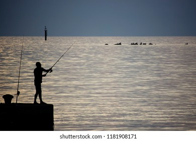 Relaxed fisherman silhouette on the pier at blue hour