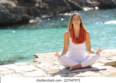 Relaxed girl doing yoga exercises on holidays in a tropical beach