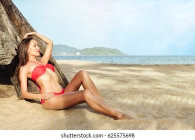 Relaxed girl enjoying tropical beach near dry old tree.Beautiful Brunette young attractive girl in red bikini sunbathing on a beach