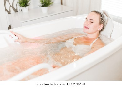 Relaxed girl in lingerie lies in white Jacuzzi in beauty salon taking care of her body