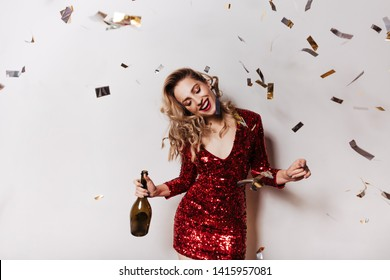 Relaxed girl in sparkle red dress celebrating birthday. Graceful caucasian woman dancing with bottle of champagne.