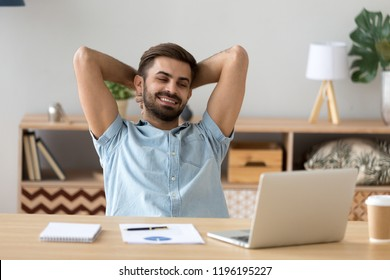 Relaxed glad businessman or business owner holding hands behind head looking at laptop smiling in office at workplace. Concept of successful deal, good job and end of the working day no stress at work