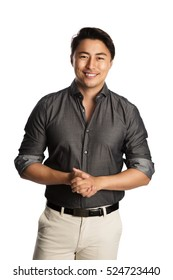 Relaxed good looking man standing against a white background wearing a grey shirt, smiling looking at camera.