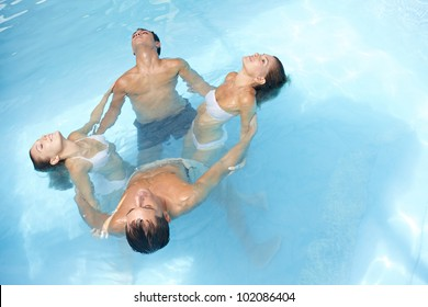 Relaxed group doing water yoga in blue swimming pool