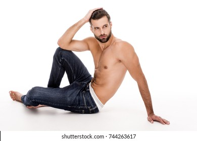 Relaxed and handsome. Full length of handsome shirtless young man in jeans looking away while sitting against white background