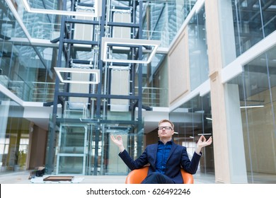 Relaxed handsome german young business man sitting and meditating on office chair. Businessman and office worker resting during a break from stressed work