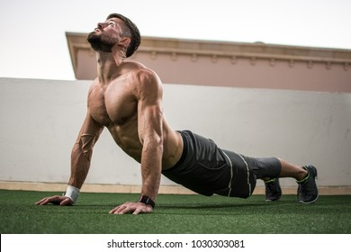 Relaxed handsome man doing yoga exercise in cobra pose outdoors.