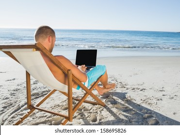 Relaxed handsome man working on his laptop on the beach