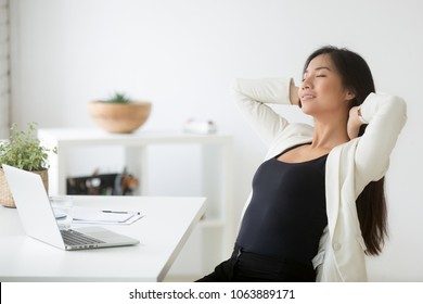 Relaxed happy asian woman enjoying break at workplace, calm smiling korean employee relaxing from computer holding hands behind head breathing air, positive thinking, feeling no stress free at work