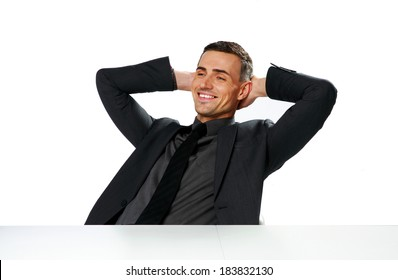 Relaxed happy businessman sitting at the table isolated on a white background