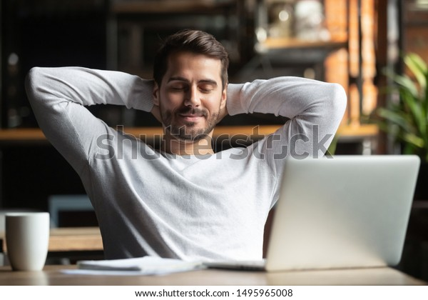 Relaxed happy businessman student worker lounge at work desk cafe table meditating, positive calm man relax break hold hand behind head dream rest from computer stretch feel no stress peace of mind