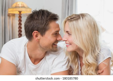 Relaxed happy casual young couple resting in bed at home