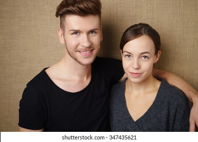 relaxed happy couple with arms around each other against light brown background