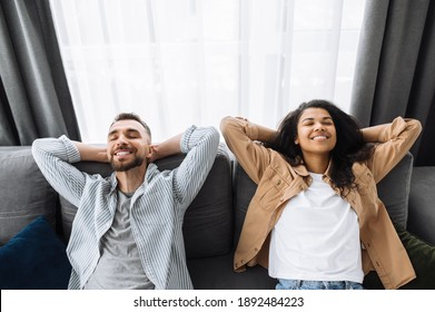 Relaxed happy couple enjoying of the rest at home on comfortable couch. Multiracial couple have lazy leisure, they relax on the couch with their eyes closed in the living room enjoying the weekend.
