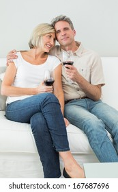 Relaxed happy couple with wine glasses sitting on sofa at home
